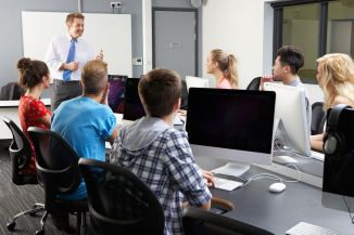 Group Of Students With Male Tutor In Computer Class